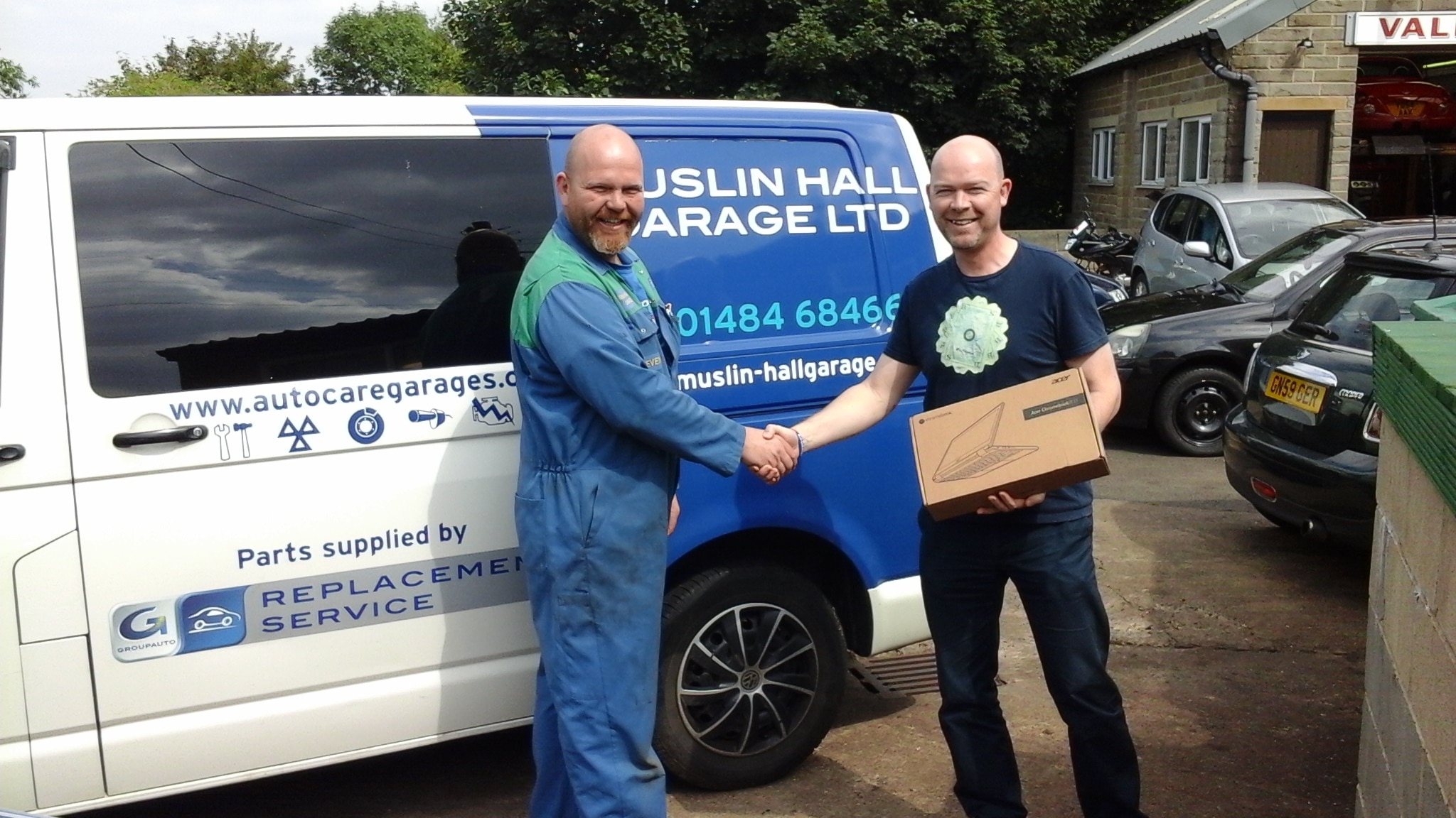 Our Auto Care Garages Summer Giveaway winner 2016 - Russell Briggs being presented with his laptop computer prize by Steven Parr of Muslin Hall Garage